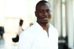 Ritratto dell'uomo afroamericano di affari con i quadri che lavorano nel fondo Immagini Stock