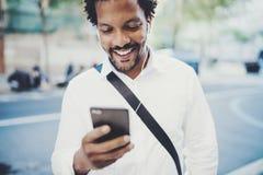 Ritratto dell'uomo afroamericano felice in cuffia che cammina alla città soleggiata e che gode alla musica sul suo smartphone Fotografia Stock Libera da Diritti