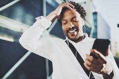 Ritratto dell'uomo afroamericano sorridente nello standidng delle cuffie in via soleggiata che gode alla musica sul suo Smart Pho Fotografie Stock