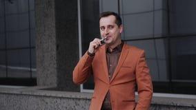 Ritratto dell'uomo allegro che fuma con la e-sigaretta all'aperto archivi video