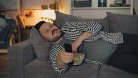 Ritratto dell'uomo allegro che guarda TV sorridere e mangiare popcorn alla notte a casa stock footage