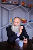 Ritratto dell'uomo anziano astuto che riflette su vita e wi di posa Fotografie Stock
