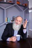 Ritratto dell'uomo anziano astuto che riflette su vita e wi di posa Immagini Stock Libere da Diritti