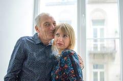 Ritratto dell'uomo anziano che sta vicino alla finestra con la sua giovane moglie Bionda-dai capelli in vestito caldo Coppie con  immagine stock libera da diritti