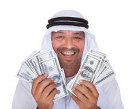 Ritratto dell'uomo arabo maturo che tiene i dollari Immagine Stock