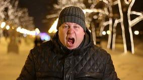 Ritratto dell'uomo arrabbiato che grida all'aperto durante la sera fredda di inverno video d archivio