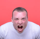 Ritratto dell'uomo arrabbiato che grida contro il fondo rosso Fotografie Stock