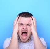 Ritratto dell'uomo arrabbiato che grida e che tira capelli contro le sedere blu Fotografie Stock