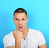Ritratto dell'uomo arrabbiato che grida mostrando pugno contro il backgr blu Immagini Stock
