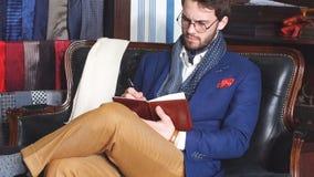 Ritratto dell'uomo attraente in cappotto scuro e del vestito nei sarti d'avanguardia all'interno stock footage