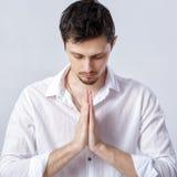 Ritratto dell'uomo attraente con capelli scuri in camicia bianca nell'yoga Immagini Stock