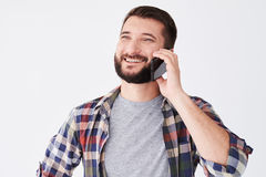 Ritratto dell'uomo barbuto allegro che sta e che parla sul cellulare Fotografia Stock Libera da Diritti