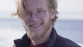 Ritratto dell'uomo barbuto bello in vetri con attaccare capelli biondi che guardano nella macchina fotografica che sorride vicino stock footage