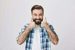 Ritratto dell'uomo barbuto felice con il sorriso brillante che mostra buon o gesto perfetto con i pollici su, sopra il fondo grig Fotografia Stock