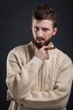 Ritratto dell'uomo barbuto sospettoso con il sigaro Immagini Stock