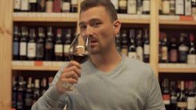 Ritratto dell'uomo bello che beve vino rosso L'uomo scuote la sua bevanda, alza di vetro di vino e prende una sorsata di vino con stock footage