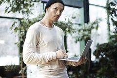 Ritratto dell'uomo bello dei pantaloni a vita bassa che lavora al computer portatile all'aperto in parco Concetto di affari Fotografie Stock