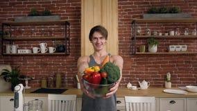 Ritratto dell'uomo bello muscolare sorridente che tiene ciotola di vetro con gli ortaggi freschi mentre stando al tavolo da cucin video d archivio