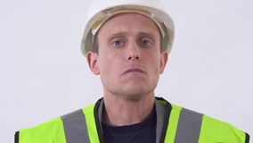 Ritratto dell'uomo bello sicuro di sé in panno e cappello della costruzione Fucilazione nello studio su un fondo bianco stock footage