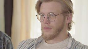 Ritratto dell'uomo biondo sicuro con gli occhi azzurri che beve birra all'interno che distoglie lo sguardo Uomo barbuto nel goder archivi video