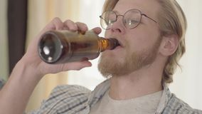 Ritratto dell'uomo biondo sicuro con gli occhi azzurri che beve birra all'interno che distoglie lo sguardo Uomo barbuto nel goder video d archivio