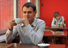 Ritratto dell'uomo in caffè con la tazza di caffè Immagini Stock Libere da Diritti