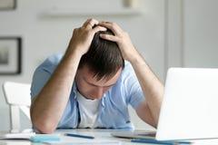 Ritratto dell'uomo che afferra il suo capo nella disperazione vicino al computer portatile Fotografie Stock Libere da Diritti