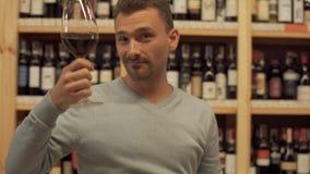 Ritratto dell'uomo che beve vino rosso L'uomo mette il suo vetro molto vicino alla macchina fotografica e poi assaggia la bevanda stock footage