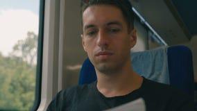 Ritratto dell'uomo che legge una rivista in un viaggio lungo del treno Viaggio in treno della vettura di concetto di viaggio dell video d archivio