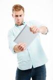 Ritratto dell'uomo che per mezzo del computer della compressa isolato su fondo bianco Fotografia Stock Libera da Diritti