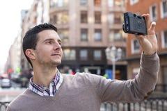 Ritratto dell'uomo che prende foto con la retro macchina fotografica nella via. Fotografia Stock