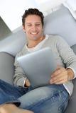 Ritratto dell'uomo che si rilassa in sofà con la compressa in mani Fotografie Stock