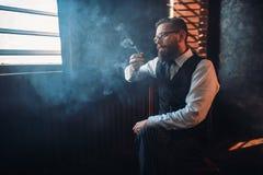 Ritratto dell'uomo che si siede sulla sedia e sul tubo di fumo Fotografia Stock