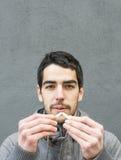 Ritratto dell'uomo che tagliato una sigaretta. immagine stock
