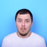 Ritratto dell'uomo con il gesto dusgusted contro fondo blu Fotografia Stock Libera da Diritti