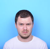 Ritratto dell'uomo con il gesto dusgusted contro fondo blu Immagini Stock