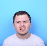 Ritratto dell'uomo con il gesto dusgusted contro fondo blu Fotografia Stock