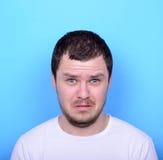 Ritratto dell'uomo con il gesto dusgusted contro fondo blu Immagine Stock