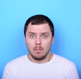 Ritratto dell'uomo con il gesto dusgusted contro fondo blu Immagini Stock Libere da Diritti