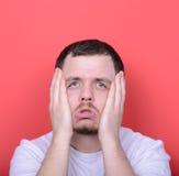 Ritratto dell'uomo con il gesto dusgusted contro fondo rosso Fotografie Stock Libere da Diritti