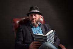 Ritratto dell'uomo con la barba e del cappello che si siede sul libro di lettura della sedia di cuoio Fotografie Stock