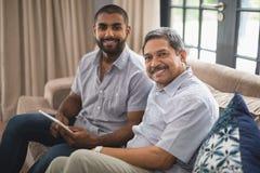 Ritratto dell'uomo con suo padre che si siede sullo strato a casa immagine stock libera da diritti