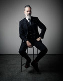 Ritratto dell'uomo d'affari adulto che indossa vestito d'avanguardia e che si siede studio sulla sedia contro la parete vuota ver immagini stock libere da diritti