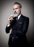 Ritratto dell'uomo d'affari adulto che indossa vestito d'avanguardia e che tiene sigaretta contro la parete vuota verticale fotografia stock libera da diritti