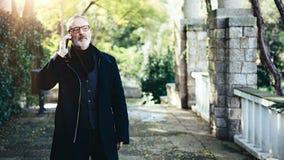 Ritratto dell'uomo d'affari adulto pensieroso che parla sul suo smartphone mentre camminando nel parco della città Orizzontale, f fotografia stock