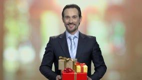 Ritratto dell'uomo d'affari allegro con i contenitori di regalo archivi video