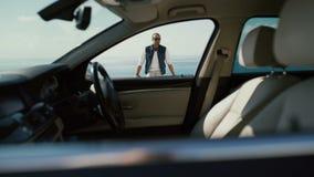 Ritratto dell'uomo d'affari attraente tramite la carrozza dell'automobile archivi video