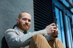 Ritratto dell'uomo d'affari barbuto con il telefono fotografie stock libere da diritti