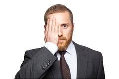 Ritratto dell'uomo d'affari bello che copre un occhio di sua mano come esamina direttamente la macchina fotografica immagini stock