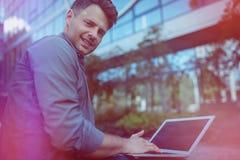 Ritratto dell'uomo d'affari bello che per mezzo del computer portatile Immagine Stock Libera da Diritti